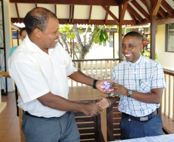 Mr Benstrong (left), representing SIM, hands over the institution's key to Mr Fanny, representing government