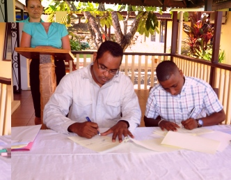 Mr Denousse and Mr Fanny sign documents marking the hand-over of the institution to the UniSey