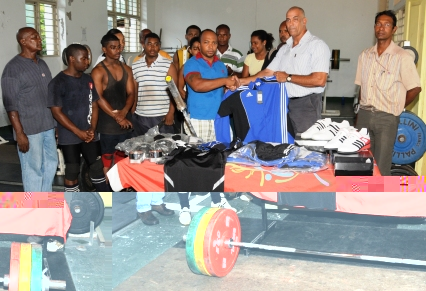 Mr Rose hands over a T-Shirt to male lifter of the year Terrence Dixie in the presence of other lifters and SWA executive committee members