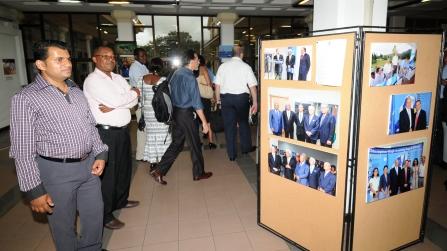 Des invités admirant quelques-unes des photos de l'exposition tournante conçue pour célébrer les 30 ans de la COI