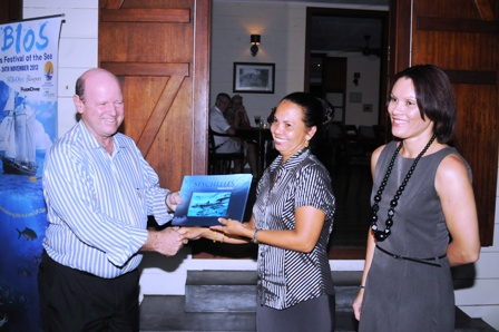 Mrs Grandcourt looks on as Minister St Ange presents a copy of the book to one of the partners who have played a role in its launch