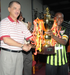 President Michel hands over the cup to St Michel captain Don Anacoura
