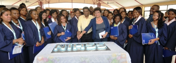 Graduates join VP Faure and Minister Mondon in cutting the cake to mark the occasion