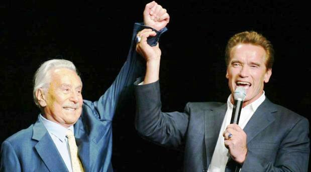 Arnold Schwarzenegger (right) raising the arm of Joe Weider