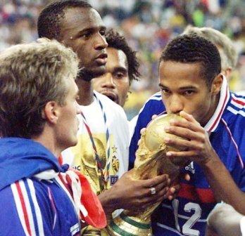 Thierry Henry embrasse la Coupe du Monde, entouré de Patrick Vieira (2ème de la gauche) et Didier Deschamps (gauche)