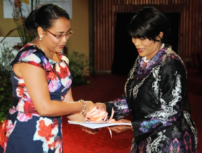 Mrs Marope receiving a copy of the ECCE national plan of action from IECD chief executive Shirley Choppy
