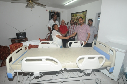 Greg's mother accepting the bed from a Kannu's Group representative