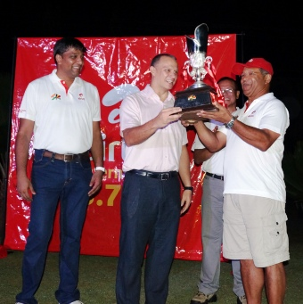 Minister Adam hands over the winner's trophy to Micock
