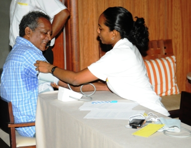 A nurse checks the BP of a health worker