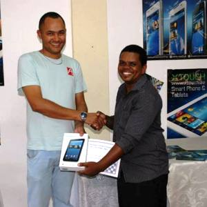 Hoareau receiving his X-Touch tablet from an X-Touch Seychelles representative