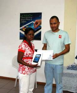 Figaro receiving her X-Touch tablet from and X-Touch Seychelles representative